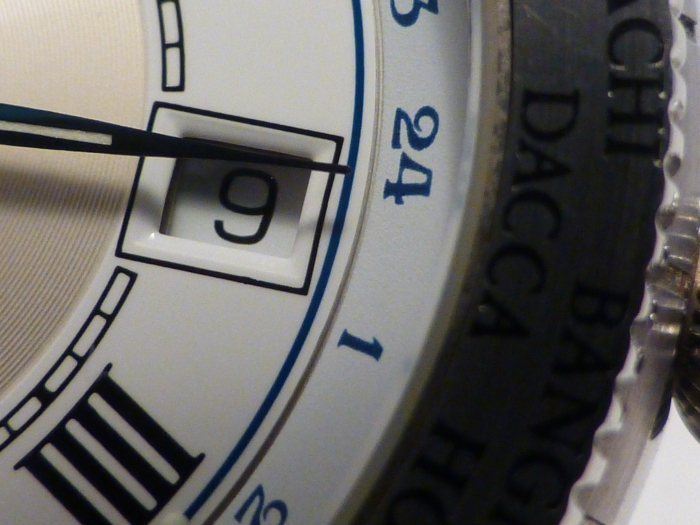 Curve cut enamel date window with GMT disc wheel outer index